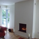 Inset contemporary gas fire burning in newly furnished room