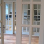 Glass doors separating lounge, dining & kitchen areas