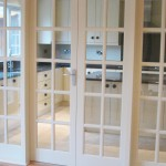 Glass windows & double doors separating dining area from kitchen