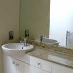 En suite with counter basin unit set in granite on fitted unts with full wall mirror