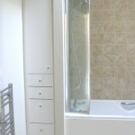 Finished bathroom showing floor to ceiling titted draw & wall unit