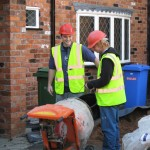 Front of property mixing concrete during extension build