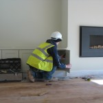 Joiner fitting cupboard to lounge alcoves
